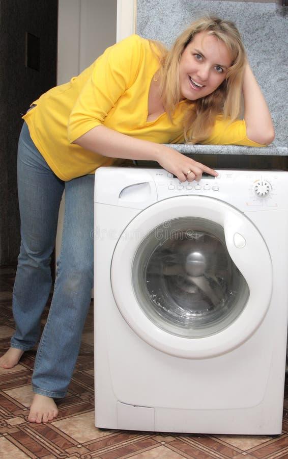 Mashine proche de lavage de fille heureuse photographie stock