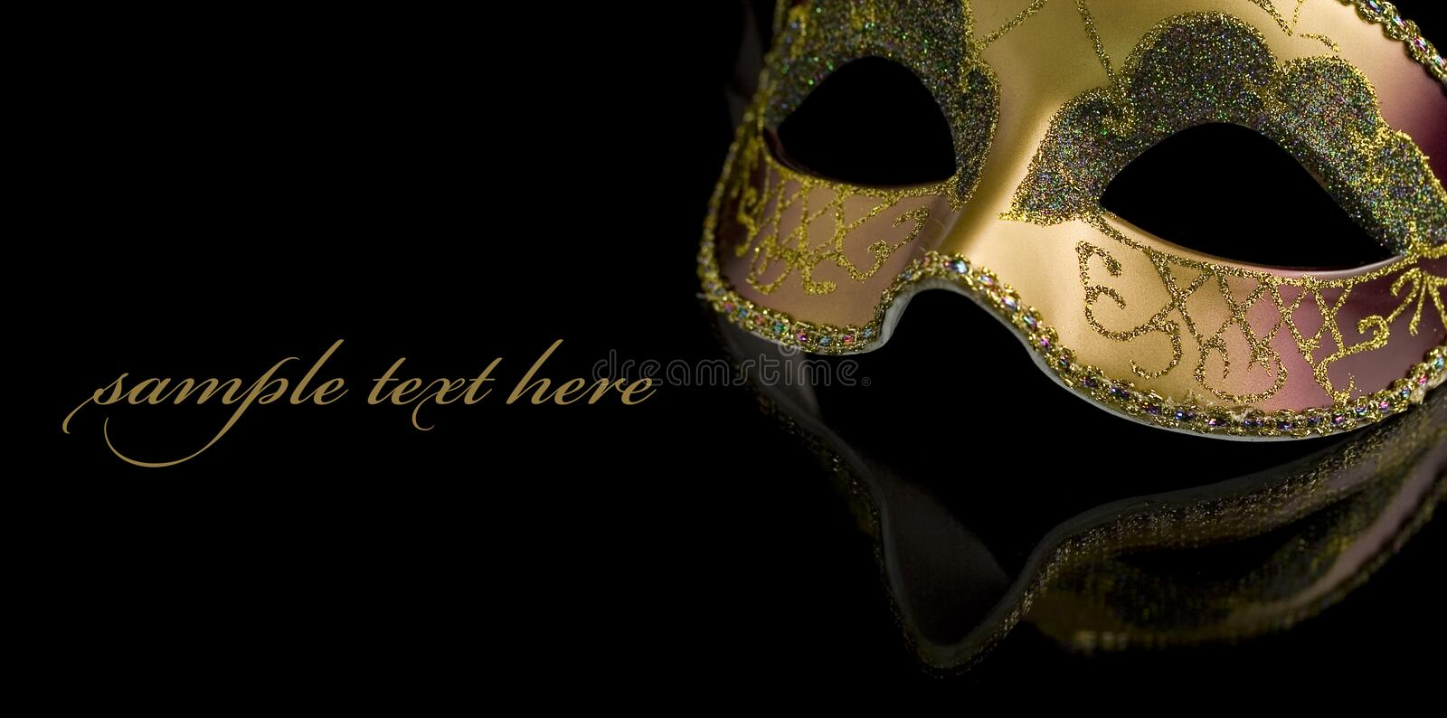 Mask. Carnival mask on a black background. The part of mask is reflected by the glass surface (with sample text stock photo