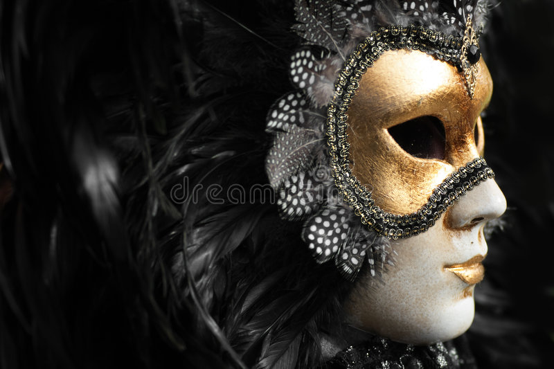Mask. Venetian mask decorated with gold leaf and embedded with fowl feathers royalty free stock image