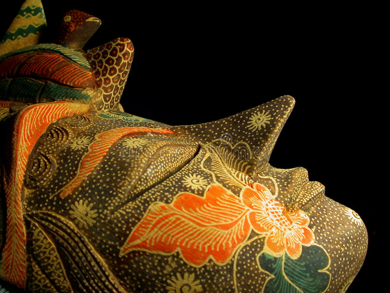 Mask on Black Background. Close up photo of a beautiful hand carved, hand painted Balinese Mask from Bali Indonesia. Focus in the image is on the outline of the