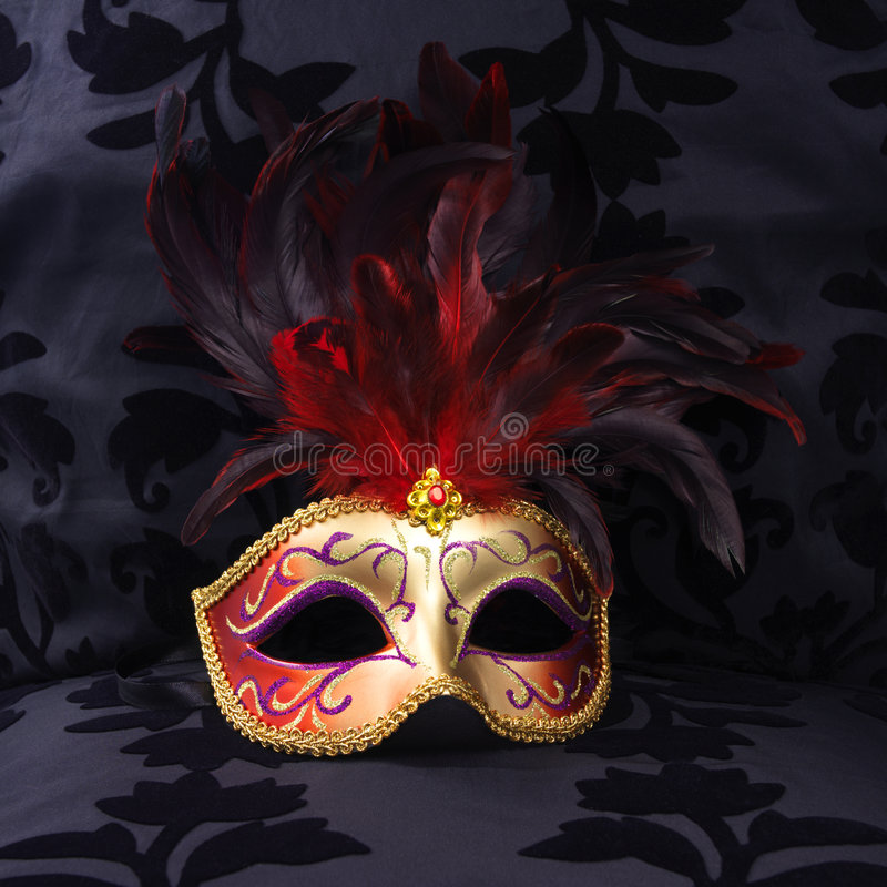 Mask at a black velvet seat (Venice, Italy). Golden and red colored mask at a black velvet seat (Venice, Italy stock images
