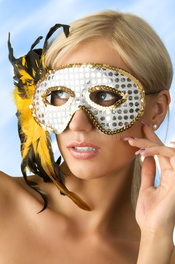 The mask and blond. Nice blond woaman with glitter silver mask and yellow feather royalty free stock image