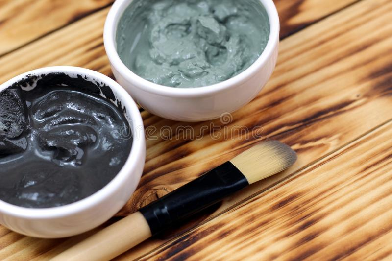 Two plates with clay and tassel mask. Mask, clay, black, green, brush, for the face, for the skin, anti-aging, healthy, nourishing, moisturizing, hygroscopic stock photo
