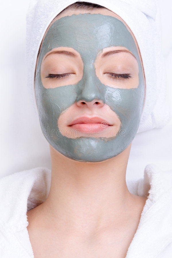 Mask of clay on the young beautiful female stock image