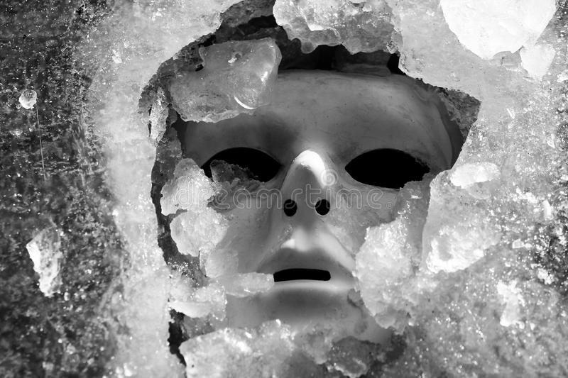 Mask and ice shards. Depressive mask of a human face and ice shards in frosty and winter time stock image
