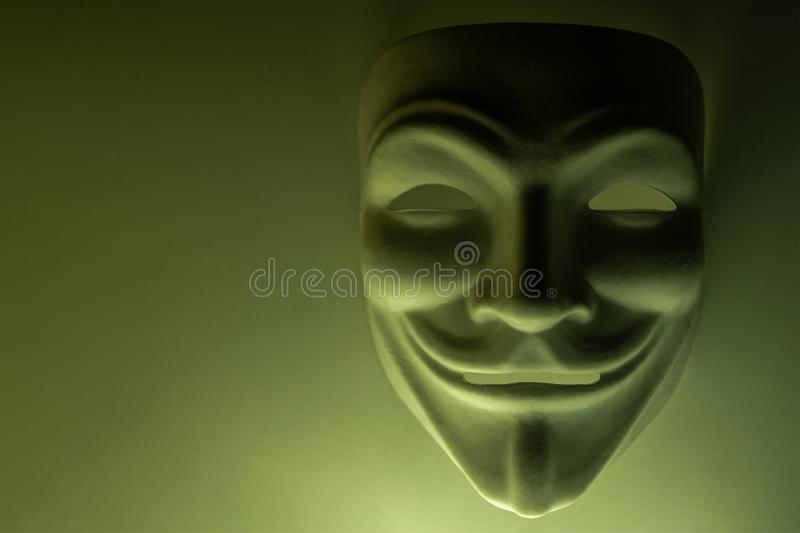 A mask that looks like a symbol of a group of hackers Anonymous. Tinted in olive color. Close-up. Shooting a subject in a dark key stock photography