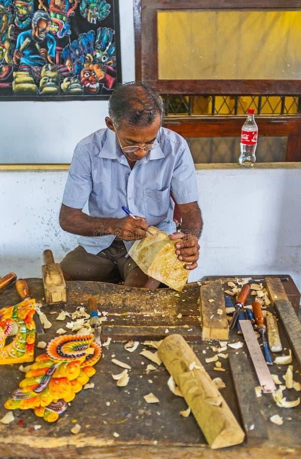The mask making in Sri Lanka. AMBALANGODA, SRI LANKA - DECEMBER 5, 2016: The artisan in process of mask making in the workshop of the Mask Museum, on December 5 stock image