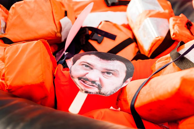 Barcelona, spain- 14 july 2019: mask of salvini face  drowning inside rubber dinghy with life belts and proactiva open arms stock photography