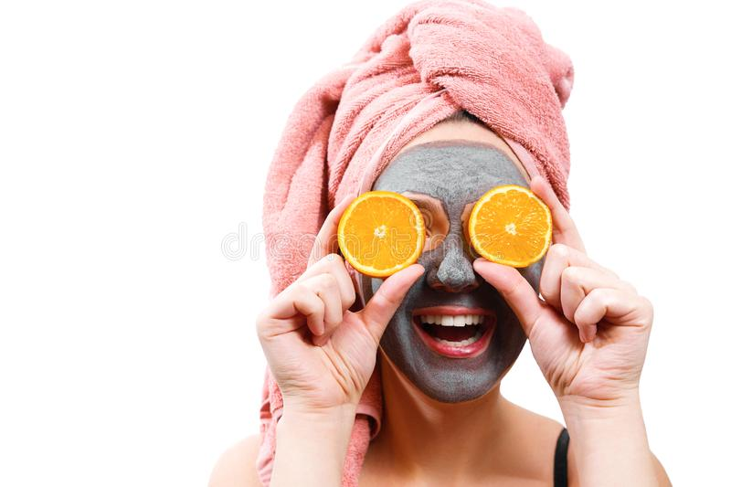 Mask for skin woman, happy and funny girl makes a mask for face skin, girl closes her eyes with orange, girl is smiling, royalty free stock photos