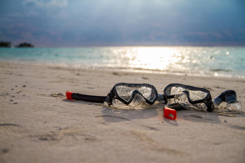 Mask and snorkel lying on sandy beach. Bokeh background. royalty free stock photos