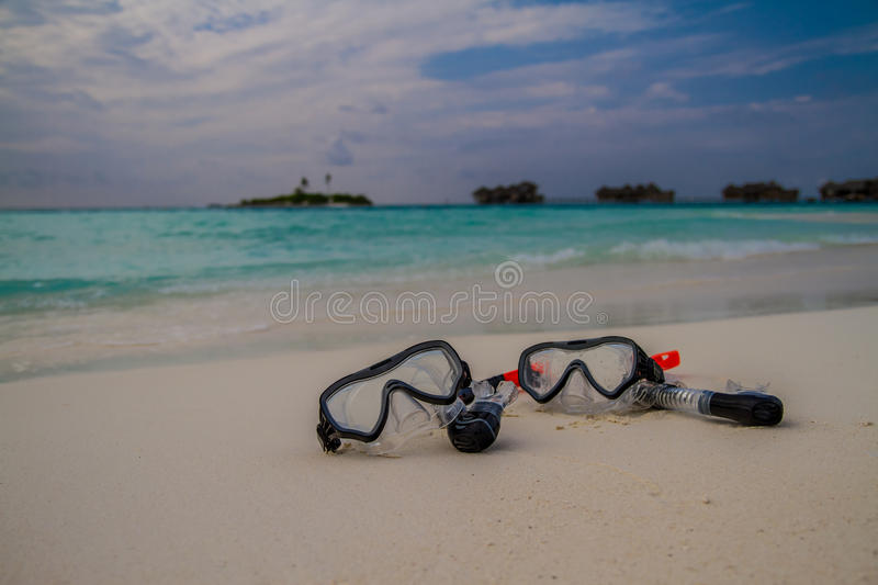 Mask and snorkel lying on sandy beach. Sea waves background. royalty free stock image