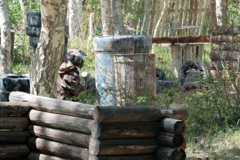 Maske, Waffen, Tarnung vom Spieler während des Spiels von Paintball Warten auf den Feind im Hinterhalt Reifen, Fässer stockfotos