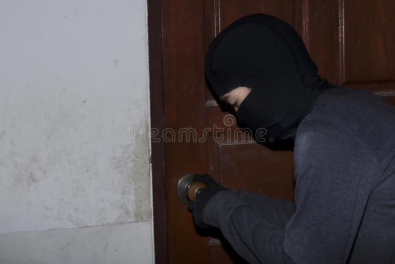 Masked burglar with lock picking tools breaking and entering into house. Crime concept royalty free stock photography