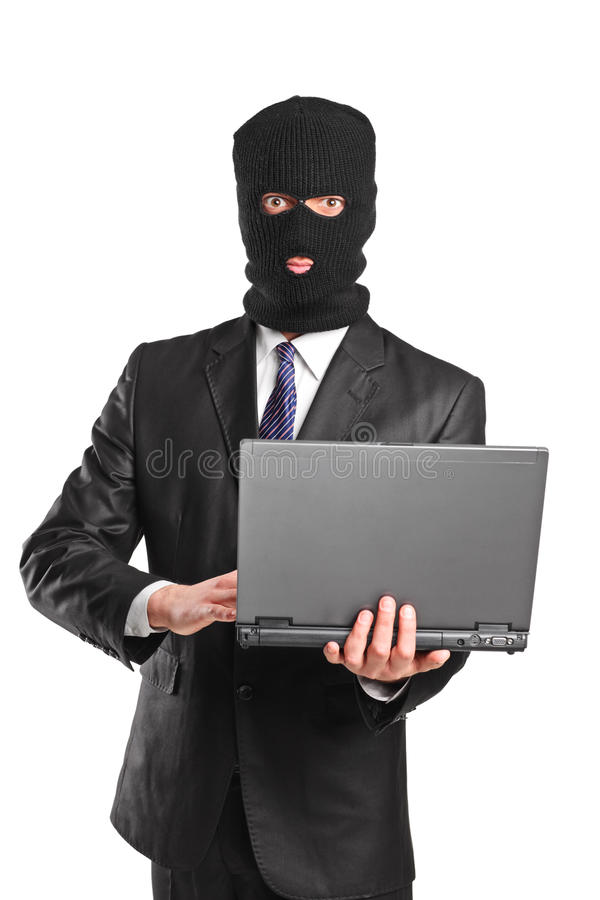 Masked businessman holding a laptop royalty free stock photo