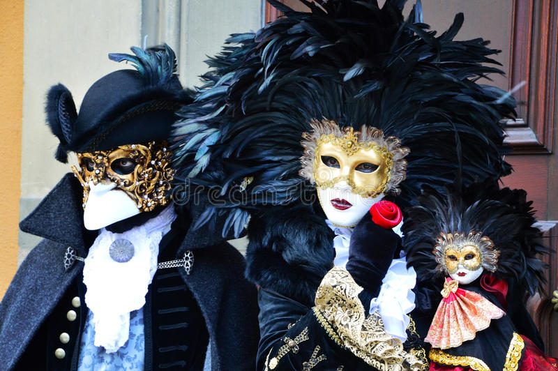 Masked couple in Renaissance costumes. Picture of a man and a woman dressed in renaissance clothes, wearing masks and looking like they want to conspire against royalty free stock photo
