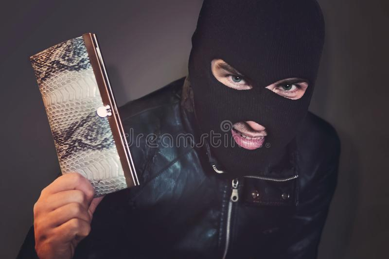 Masked criminal at the black background grins looking at the viewer and showing a purse in hand. Evil-doer is glad to. Have a stolen leather wallet. A satisfied stock photo