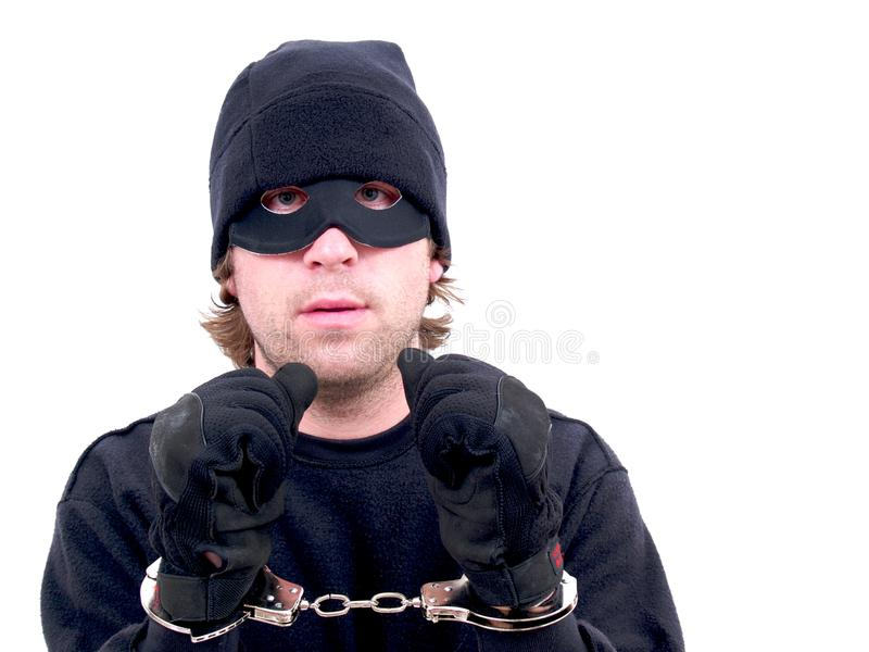 A masked criminal handcuffed royalty free stock photos