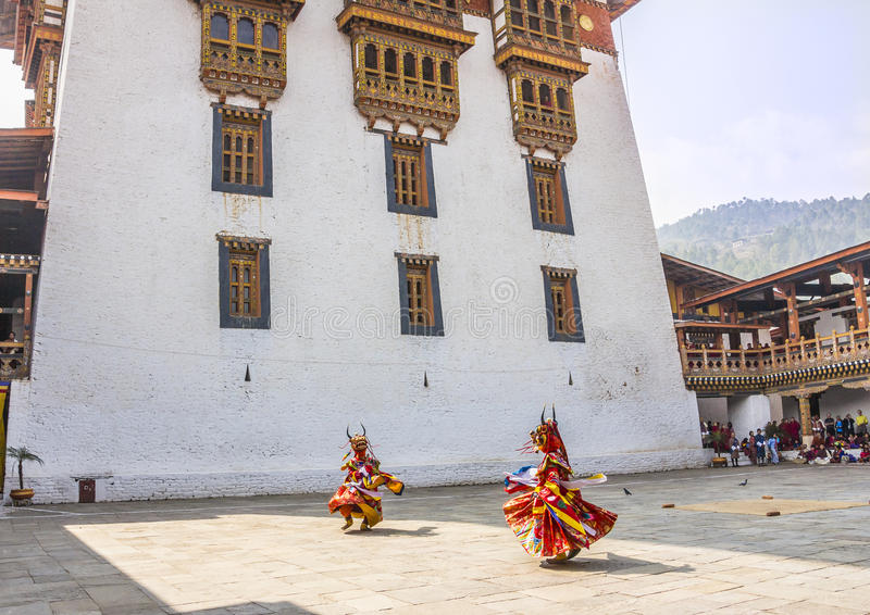 Masked dancers. Two masked dancers at drupchen festival in the dzong of Punakha, Bhutan. Drupchen festival is taking place yearly in march. (all faces blurred stock photo