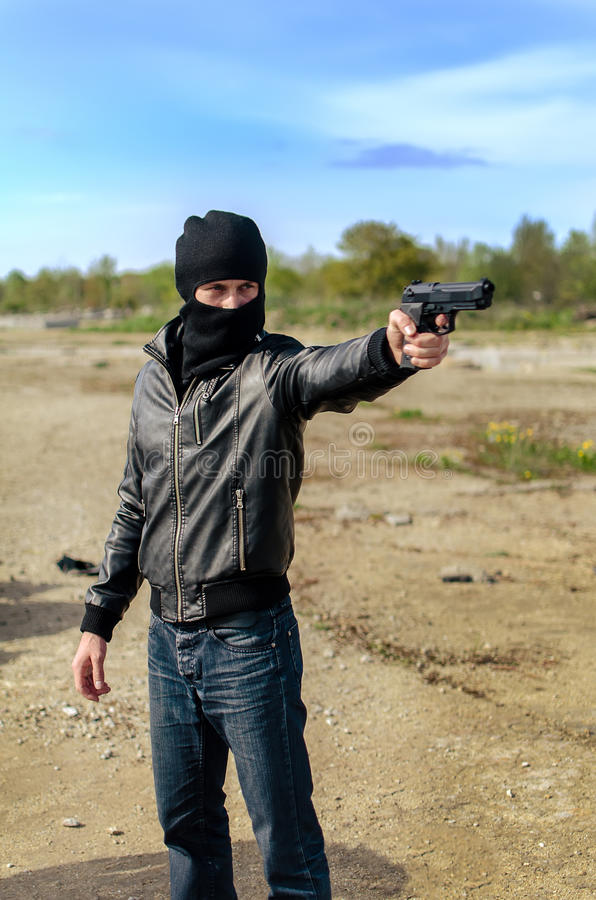 Masked gunman. Taking aim with a gun royalty free stock photo
