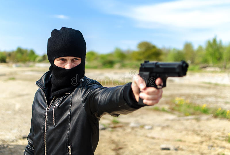 Masked gunman. Taking aim with a gun royalty free stock photos