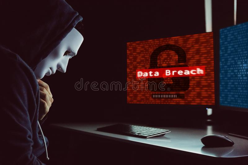 Masked hacker under hood using computer to commit data breach cr. Ime - internet computer crime concept royalty free stock photography