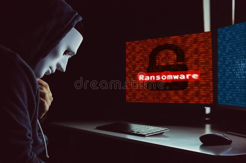 Masked hacker under hood using computer to hack into system and. Employ ransomware - internet computer crime concept royalty free stock photo