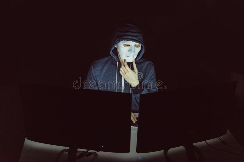 Masked hacker under hood using computer to hack into system and trying to commit computer crime. Masked hacker under hood using computer to hack into system and stock images