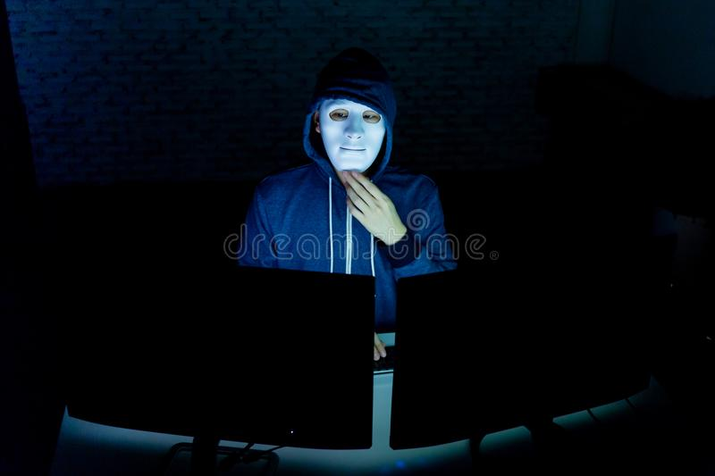 Masked hacker under hood using computer to hack into system and trying to commit computer crime. Masked hacker under hood using computer to hack into system and royalty free stock images
