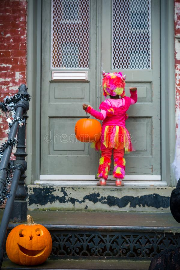 Masked Little Girl Knocking a Door Asking for Sweeties During Ha royalty free stock images