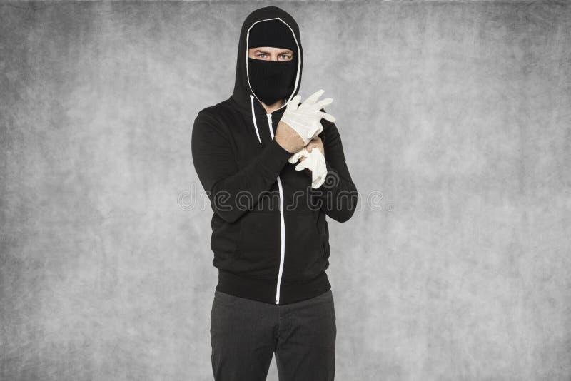 Masked man assumes plastic gloves royalty free stock photos