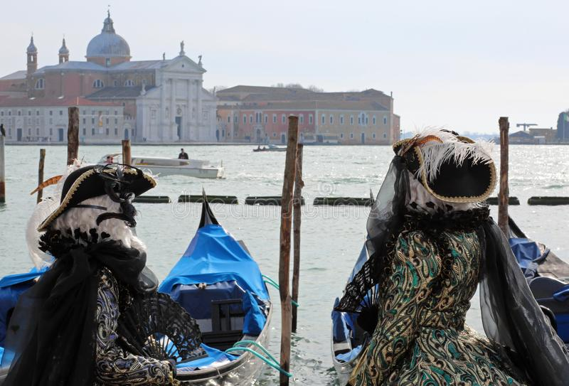 Masked people in Venice in Italy and the Church of Saint George. In Background stock photography