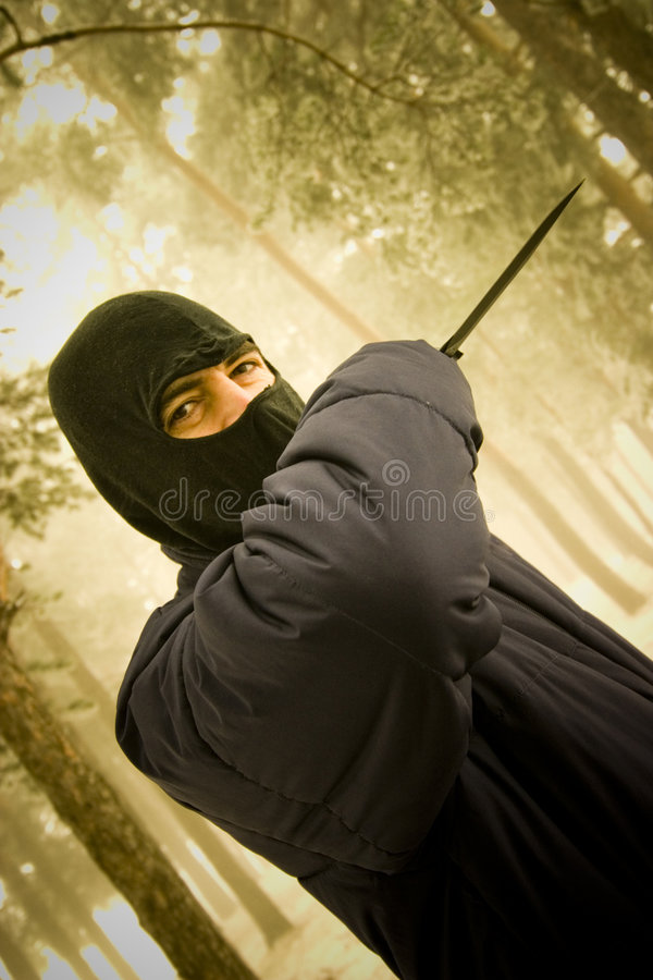 Masked person attacking with knife stock photography