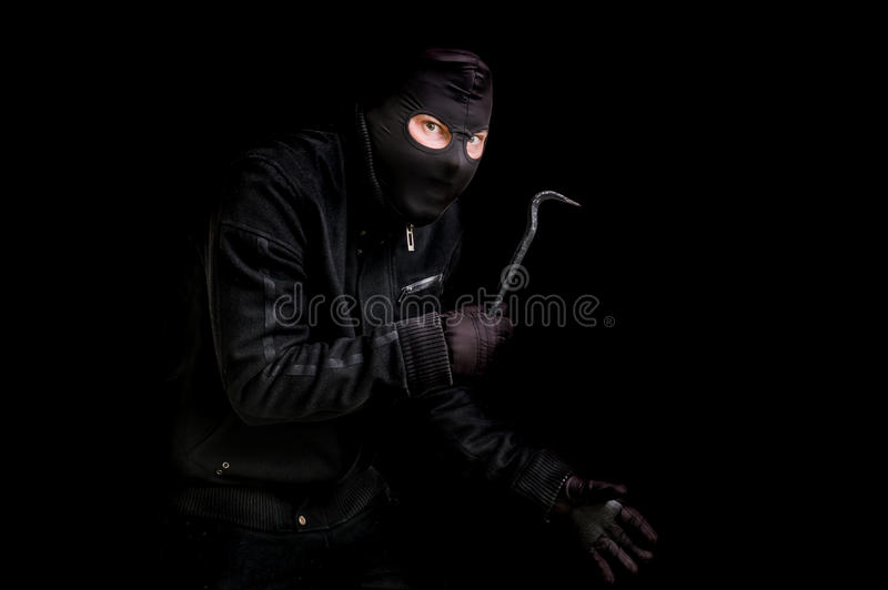 Masked thief in balaclava with crowbar isolated on black. Background royalty free stock image