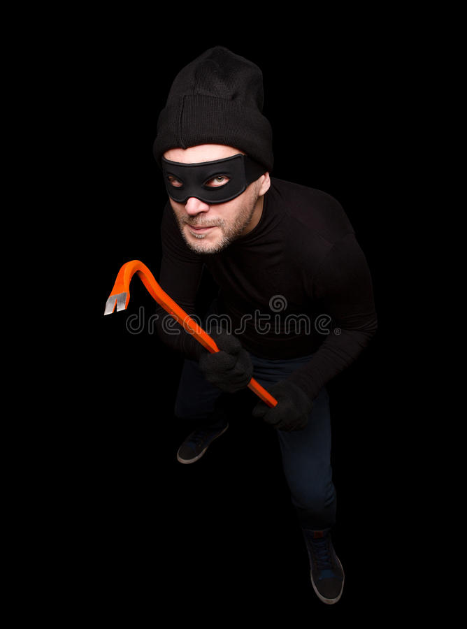 Masked thief. In balaclava is going to steal or rob house at night. Handsome man with crowbar over black background. Isolated on black royalty free stock images