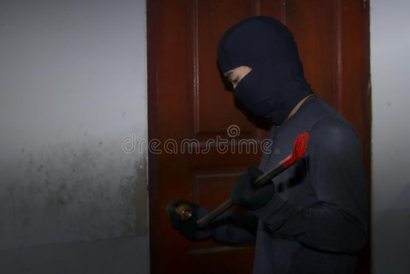 Masked thief with balaclava using crowbar to breaking into a house at night time. Crime concept. royalty free stock photo