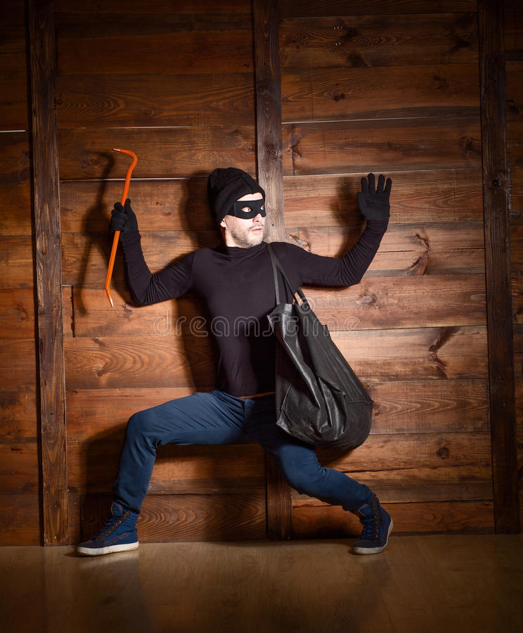 Masked thief. Masked burglar wearing black clothes was caught by police near house in which he wanted to break in stock photo