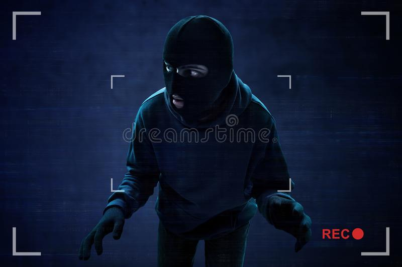 Masked thief caught on security camera. S stock photography