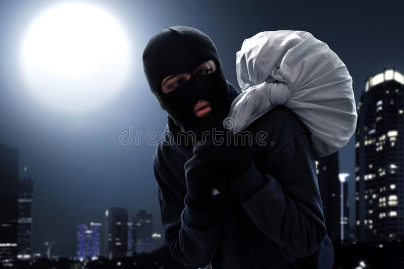 Masked thief escape at night. Masked thief escaping at night stock photos