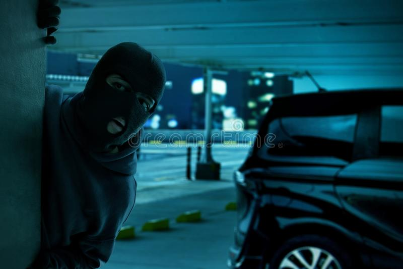 Masked thief hiding on the wall. At night royalty free stock image