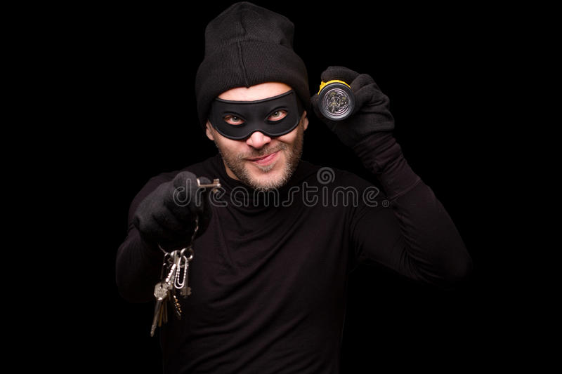 Masked thief. Portrait of masked thief holding flashlight and keys. Handsome man looking at camera over black background. Isolated on black stock images