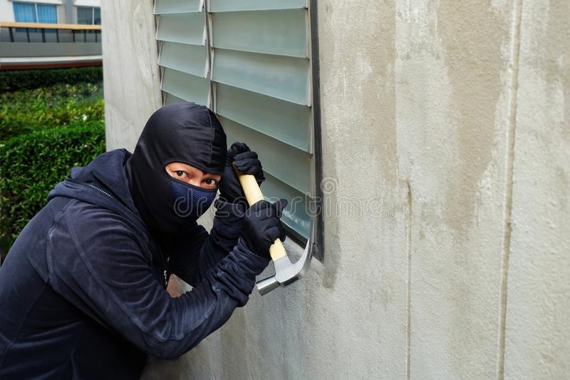 Masked thief using a hammer trying to break windows royalty free stock image