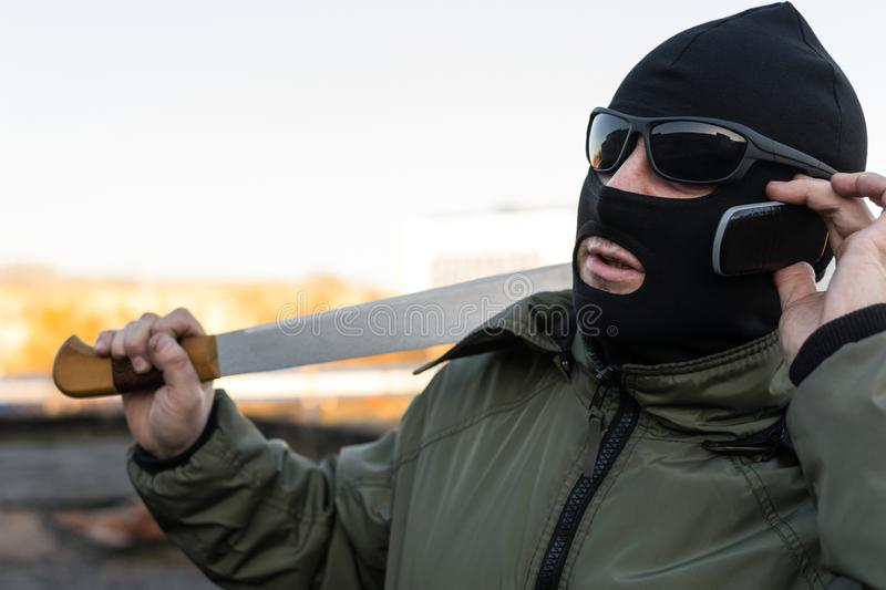 The masked thug is negotiating on a mobile phone. Bandit, robber in mask and a knife in his hands leads important negotiations on a mobile phone royalty free stock images