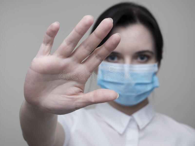 Masked woman makes stopping hand gesture. Stop coronavirus or covid 19 outbreak concept.  royalty free stock images