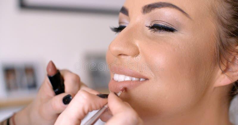 Maskenbildner Applying Lipstick zur hübschen Frau lizenzfreie stockbilder