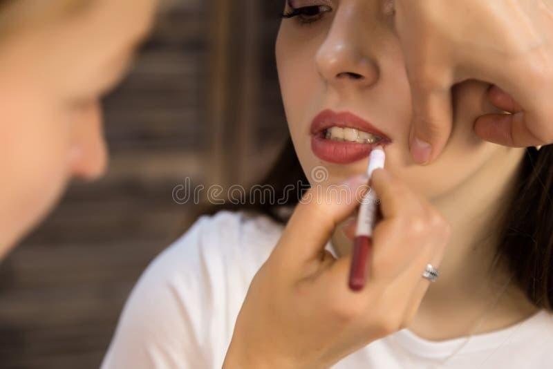 Maskenbildner, der Lippenmake-up mit Bleistift zum jungen Modell tut stockfotografie