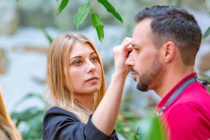 Maskenbildner, der Make-up auf Modell vor schießender Reihe anwendet stockbilder