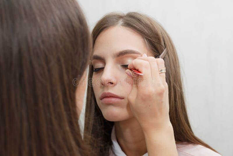 Maskenbildner klebt Bündel auf den Wimpern modellieren stockbilder