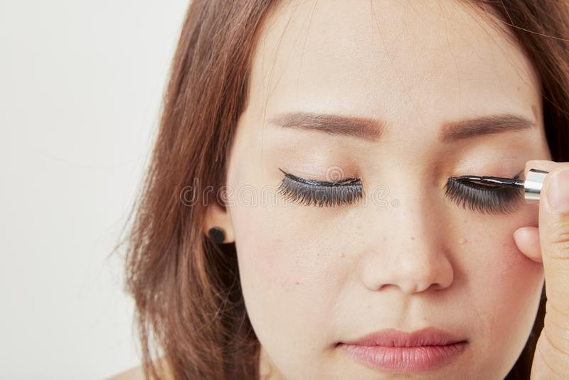 Maskenbildner klebt Wimpern auf Kunden stockbild