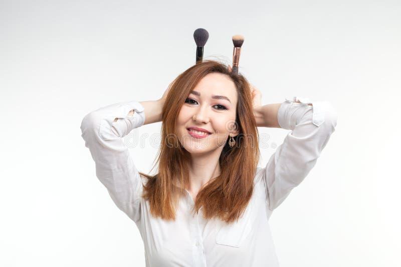 Maskenbildner, Schönheit und Kosmetikkonzept - koreanischer weiblicher Make-upkünstler, der herum mit Make-upbürsten auf Weiß täu stockbilder