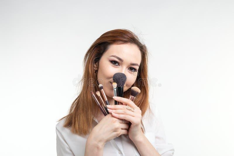 Maskenbildner, Schönheit und Leutekonzept - lustige koreanische junge Frau, die herum mit Make-upbürsten auf Weiß täuscht stockfoto